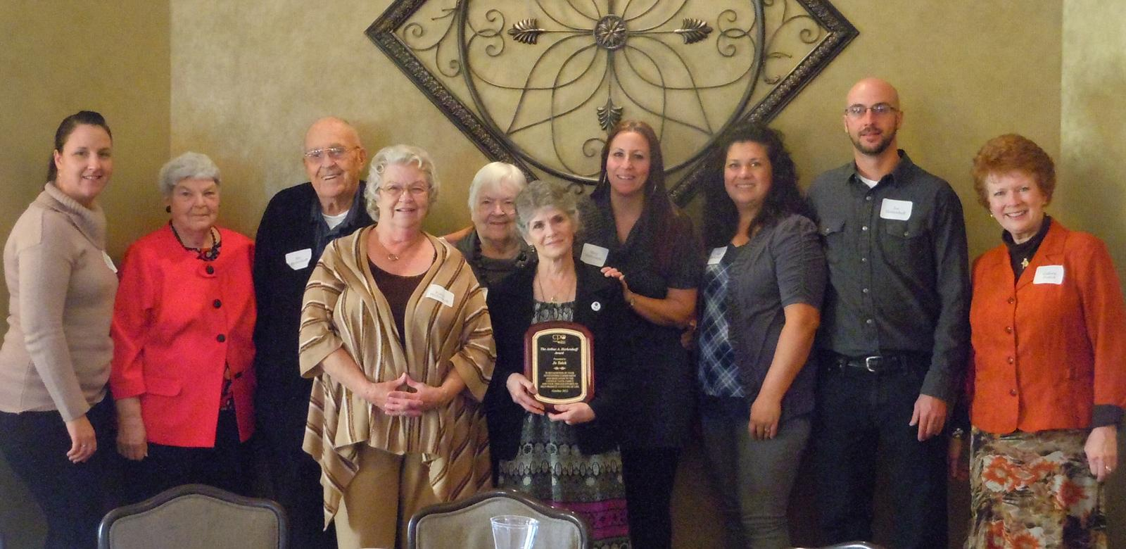 Jo Tolck with Herkenhoff family members. Left to Right: Meghan Habisch (daughter), Barb Herkenhoff (sister-in-law), Ray Herkenhoff (brother), Kathy Herkenhoff (Art's wife), Lorraine Peterson (sister), Jo Tolck, Mary Mattheison (daughter), Nikki Herkenhoff (daughter-in-law), Joe Herkenhoff (son) and Colleen Perfect, President of CPO.